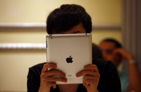A man looks at his iPad while sitting in a cafe in central Beijing June 6, 2012. Apple maintains vast market dominance int he tablet space.